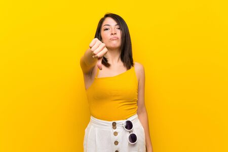 Young Mexican woman over isolated yellow background showing thumb down with negative expression 写真素材