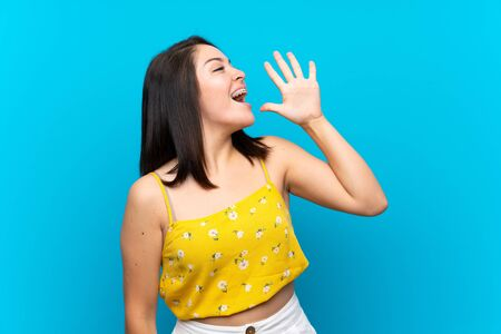 Young Mexican woman over isolated blue background shouting with mouth wide open Foto de archivo - 130158017