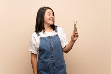 Young Mexican woman over isolated background taking a lot of money Stock Photo