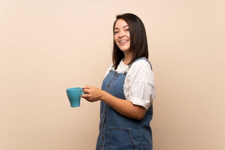 Young Mexican woman over isolated background holding hot cup of coffee Foto de archivo - 130158025