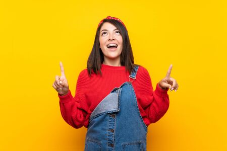 Young Mexican woman with overalls over yellow wall surprised and pointing up Foto de archivo - 130158035