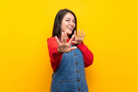 Young Mexican woman with overalls over yellow wall nervous stretching hands to the front