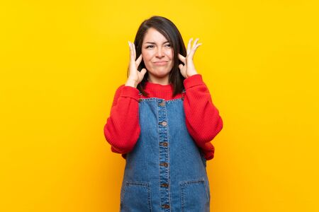 Young Mexican woman with overalls over yellow wall frustrated and covering ears