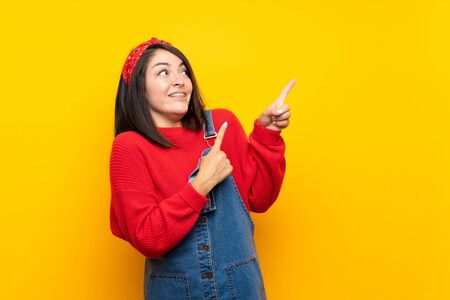 Young Mexican woman with overalls over yellow wall frightened and pointing to the side