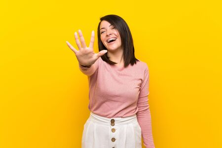 Young Mexican woman over isolated yellow background counting five with fingers