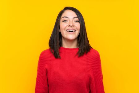 Young Mexican woman with red sweater over yellow wall with surprise facial expression Stock fotó - 130158084