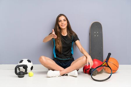 Young sport woman sitting on the floor handshaking after good deal