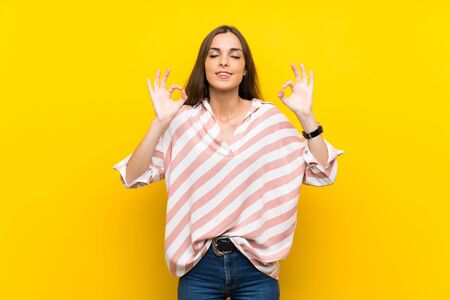 Young woman over isolated yellow background in zen pose