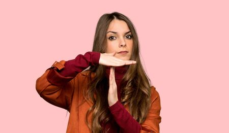 Young woman with coat making stop gesture with her hand to stop an act over isolated pink background