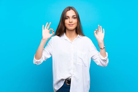 Young woman over isolated blue background in zen pose