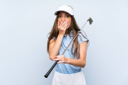 Young golfer woman over isolated blue wall with surprise facial expression Stock Photo