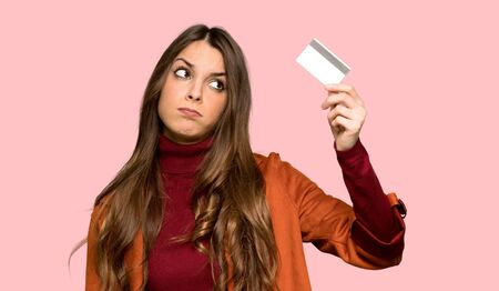Young woman with coat listening music with the phone over isolated pink background