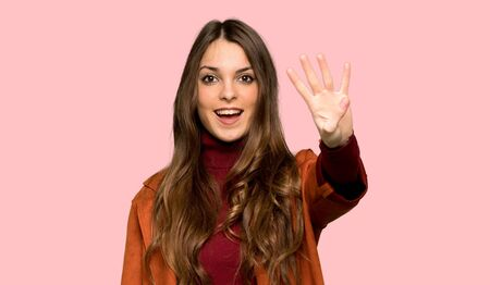 Young woman with coat happy and counting four with fingers over isolated pink background Foto de archivo - 130167445