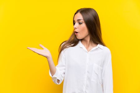 Young woman over isolated yellow background holding copyspace imaginary on the palm Archivio Fotografico