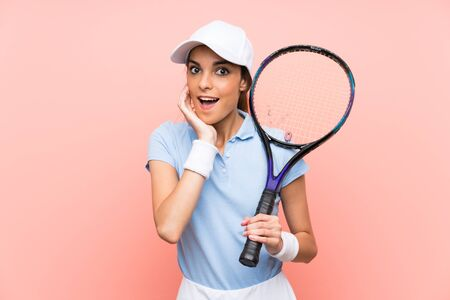 Young tennis player woman over isolated pink wall with surprise and shocked facial expression Stock Photo