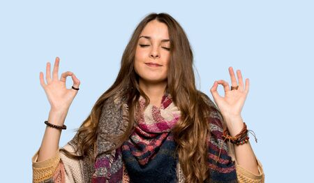 Young hippie woman in zen pose over isolated blue background