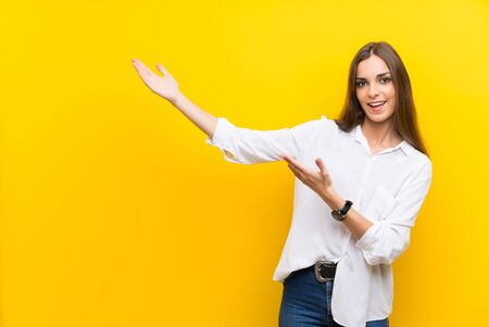 Young woman over isolated yellow background extending hands to the side for inviting to come