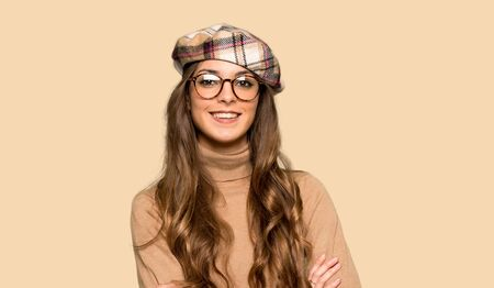 Young woman with beret keeping the arms crossed in frontal position over isolated yellow background Stok Fotoğraf