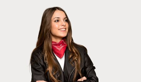 Young woman with leather jacket keeping the arms crossed while smiling over isolated grey background Stok Fotoğraf