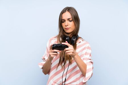 Young woman playing with a video game controller over isolated blue wall Stock Photo