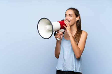 Young woman over isolated blue background shouting through a megaphone