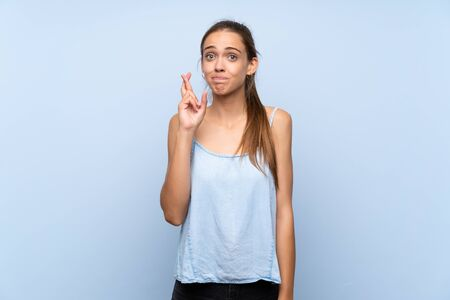 Young woman over isolated blue background with fingers crossing and wishing the best Stock fotó