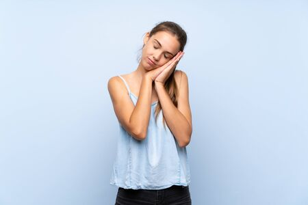 Young woman over isolated blue background making sleep gesture in dorable expression