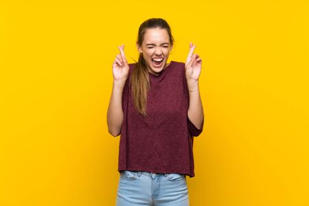 Young woman over isolated yellow background with fingers crossing