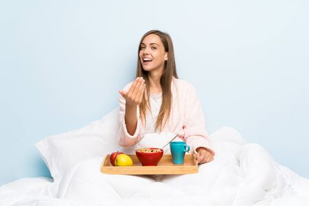 Young woman in dressing gown with breakfast inviting to come
