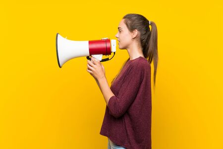 Young woman over isolated yellow background shouting through a megaphone Imagens
