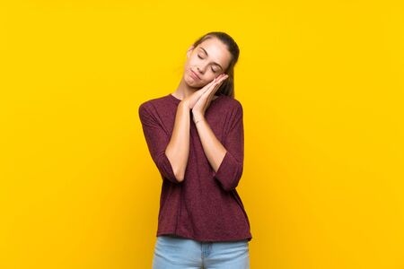 Young woman over isolated yellow background making sleep gesture in dorable expression