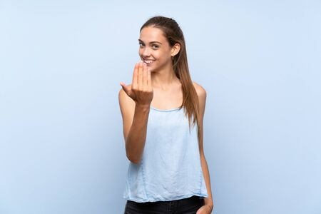 Young woman over isolated blue background inviting to come with hand. Happy that you came