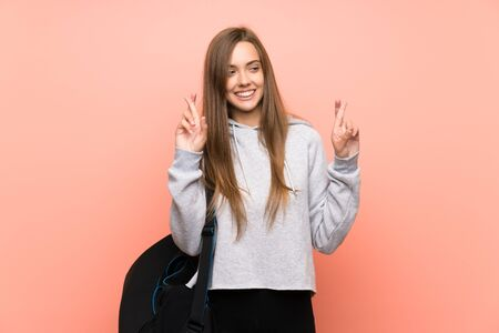 Young sport woman over isolated pink background with fingers crossing