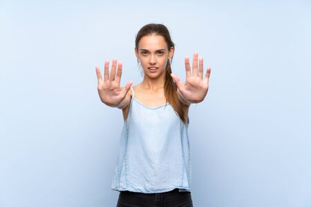 Young woman over isolated blue background making stop gesture and disappointed