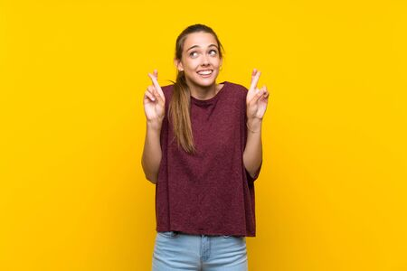 Young woman over isolated yellow background with fingers crossing and wishing the best