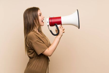Teenager girl over isolated shouting through a megaphone