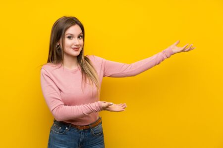 Teenager girl over isolated yellow background extending hands to the side for inviting to come
