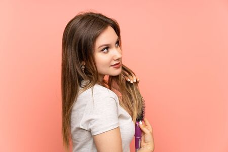 Teenager girl over pink background with hair comb Imagens