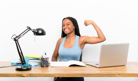 African American teenager student girl with long braided hair in her workplace doing strong gesture