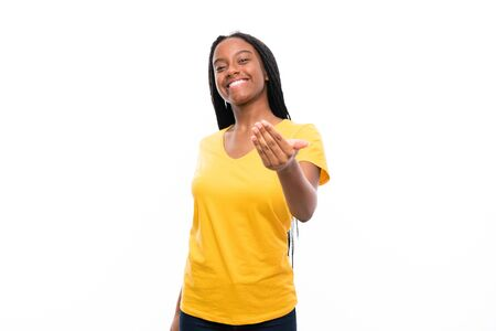 African American teenager girl with long braided hair over isolated white background inviting to come