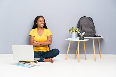 African American teenager student girl with long braided hair sitting on the floor looking to the side Stok Fotoğraf