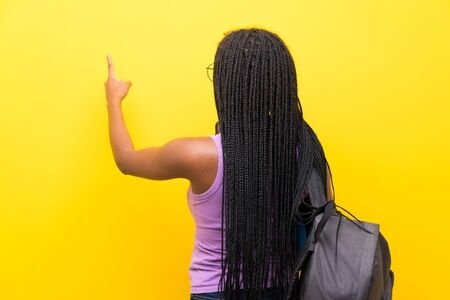 African American teenager student girl with long braided hair over isolated yellow wall pointing back with the index finger