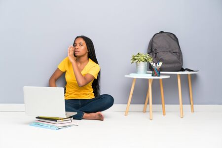 African American teenager student girl with long braided hair sitting on the floor whispering something Standard-Bild