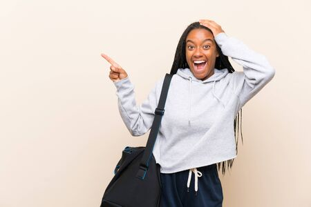 African American sport teenager girl with long braided hair surprised and pointing finger to the side