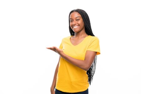 African American teenager girl with long braided hair over isolated white background extending hands to the side for inviting to come Banco de Imagens