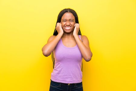 African American teenager girl with long braided hair over isolated yellow wall frustrated and covering ears