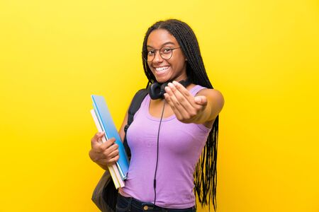 African American teenager student girl with long braided hair over isolated yellow wall inviting to come