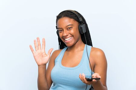 African American teenager girl with long braided hair listening music with a mobile saluting with hand with happy expression