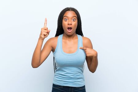 African American teenager girl with long braided hair over isolated blue background with surprise facial expression