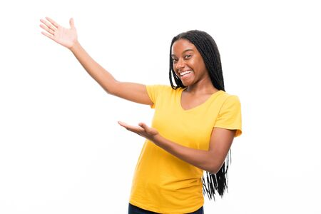 African American teenager girl with long braided hair over isolated white background extending hands to the side for inviting to come
